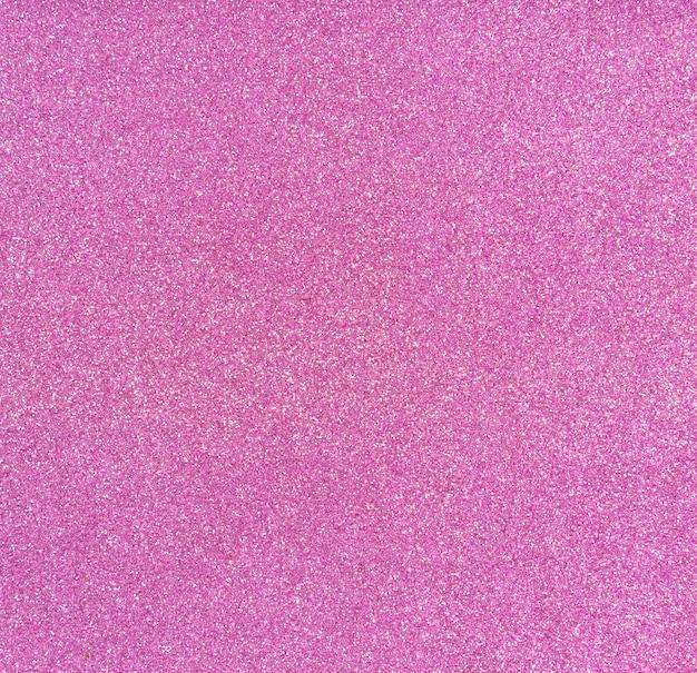 キラキラと装飾的な紙、創造性のための商品。ピンクの光沢のある背景。