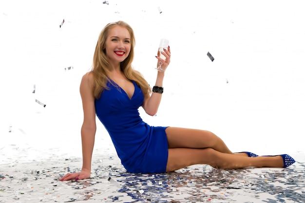 シャンパンのグラスと、パーティーのためのドレスで白でポーズ美しい少女