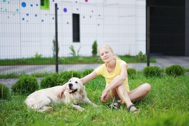 ペット、草の上に彼女の犬と一緒に休んでいる若いブロンドの女性への愛