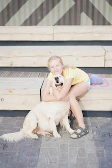 ペットを愛し、路上で彼女の犬と一緒に休んでいる若いブロンドの女性