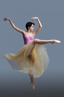 バレリーナは灰色のスタジオで踊っています