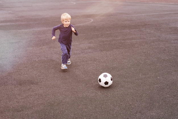 近代的な都市、スタジアムでサッカーボールで遊ぶ少年のアクティブなライフスタイル