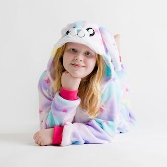 現代のファッション-着ぐるみパジャマ、バニー衣装で白でポーズ美しいブロンドの女の子