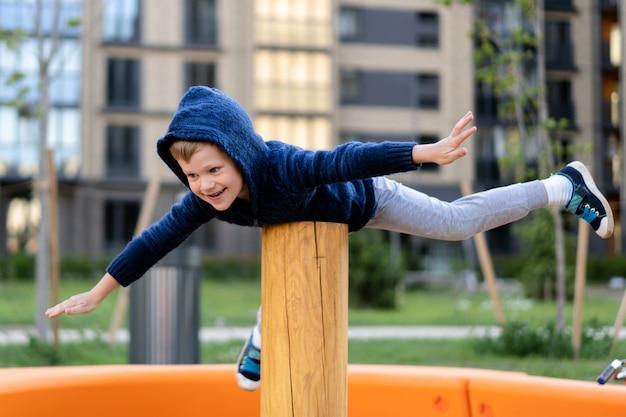 小さな男の子は、近代的な都市ヨーロッパの遊び場で遊んで楽しんでいます。