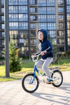 Безопасность в современном европейском городе. маленький счастливый мальчик едет на велосипеде через закрытый двор в многоэтажном городском здании.