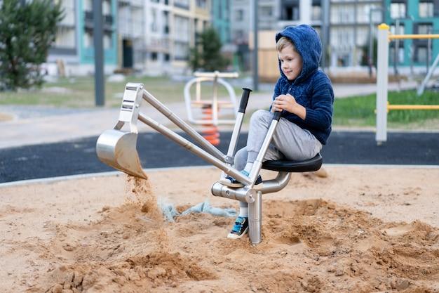 Маленький мальчик весело играет на современной городской европейской детской площадке