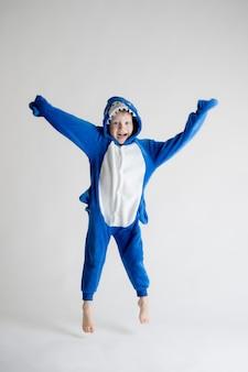 Веселый маленький мальчик позирует на белом фоне в пижаме, синий костюм акулы