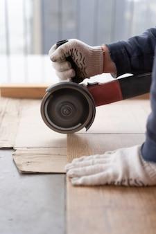 修理および装飾。男はグラインダーでセラミックタイルをカットします。