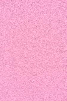 ピンクの壁の表面に装飾的なプラスターのテクスチャのクローズアップからの背景