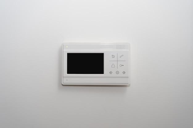 アパートの玄関近くの白い壁にあるビデオインターホン
