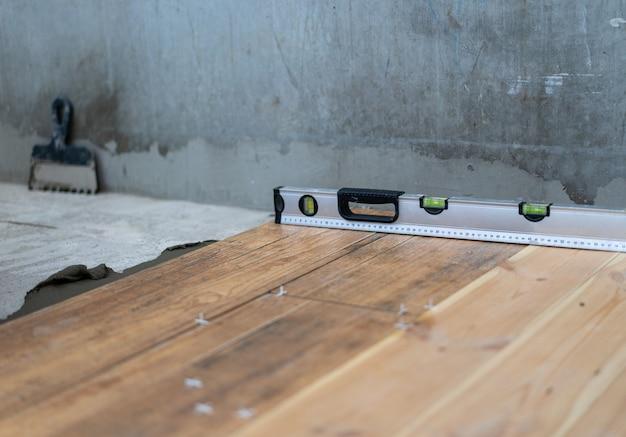 修理および装飾。瓦職人はアパートの床に磁器タイルを置きます