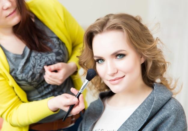 メイクアップのプロセス。モデルの顔にブラシを使用してメイクアップアーティスト。ビューティーサロンインテリアの若いブロンドの女性の肖像画。肌にトーンを適用します。