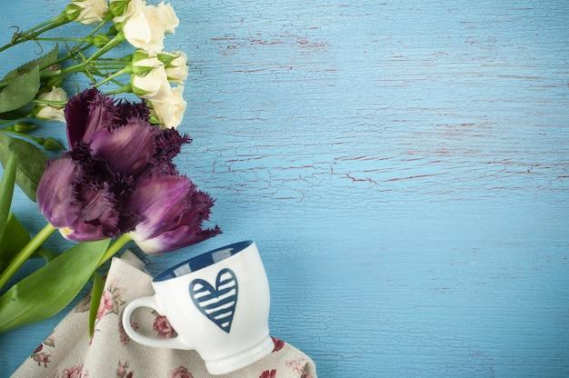 Тюльпаны и чашка на синем дереве