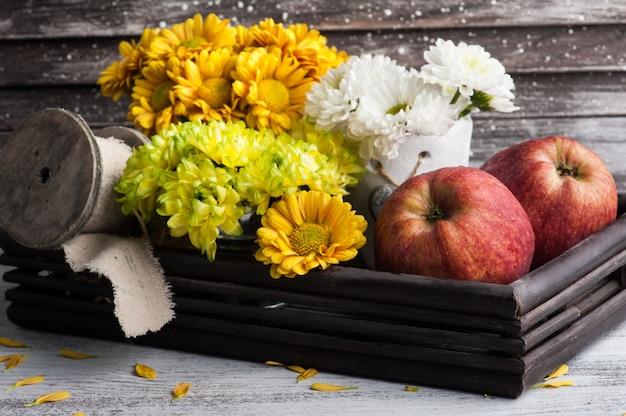 Хризантема в жестяной банке и яблоках
