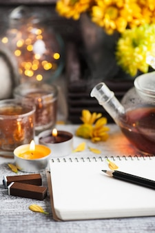 Пустая тетрадь с зажженными огнями и чайником