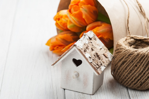 オレンジ色のチューリップ、木製のハート形の鳥の家と麻ひも