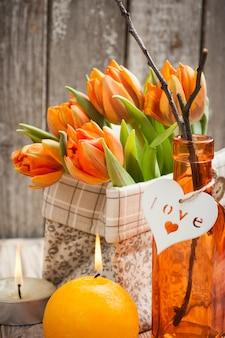Букет из оранжевых тюльпанов, зажженных свечей