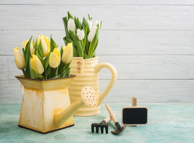 Весенние тюльпаны в желтой вазе и лейке