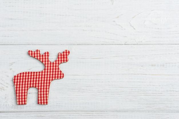 素朴な白い木製のテーブルに赤い装飾的なおもちゃ鹿