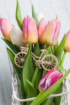 ピンクの黄色のチューリップと木製の自転車の花束