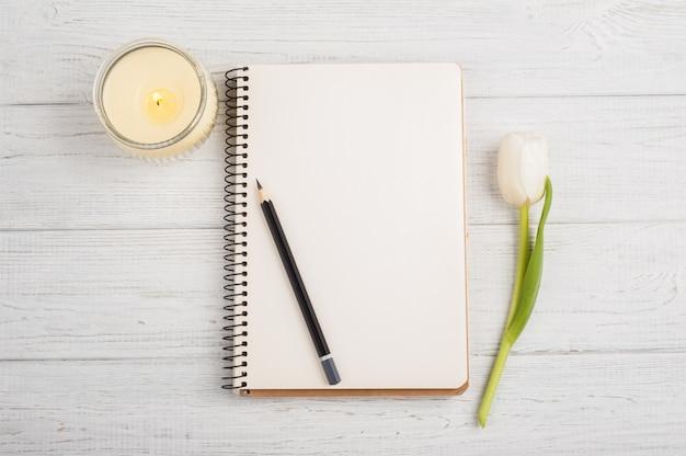 ノートブック、鉛筆、キャンドル、チューリップを開く