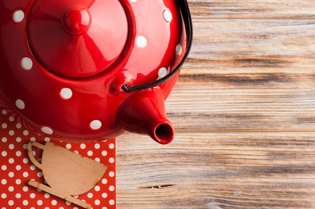 赤白の水玉ティーポットとテーブルの上の木製カップ
