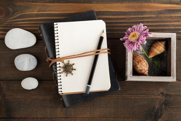 空白のノートブック、小石、貝殻、花を開く