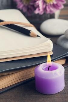Открыть пустой блокнот, зажженная свеча, цветок