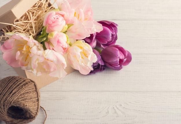 Свежие розовые тюльпаны, шпагат и коробка