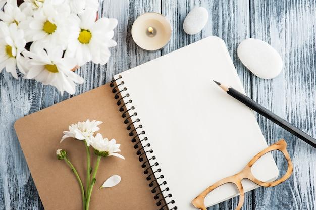 空白のノートブック、小石、花を開く