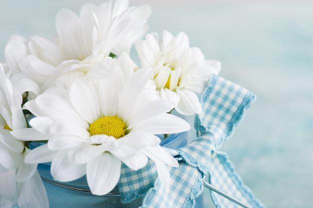 パステルブルーのテーブルに新鮮なデイジーの花のクローズアップ