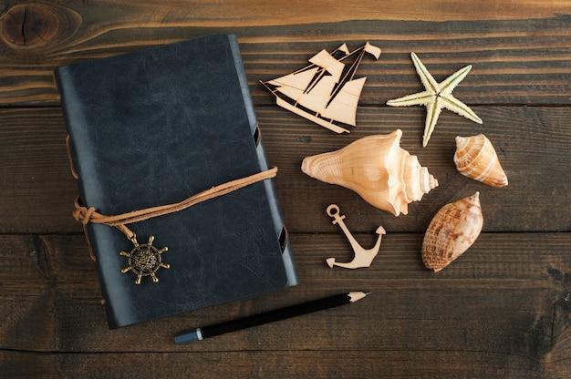 ノートブック、貝殻、木造船