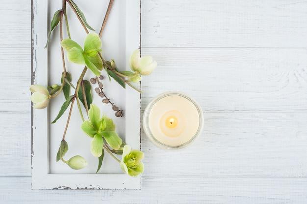 Зеленые цветы и зажженная свеча