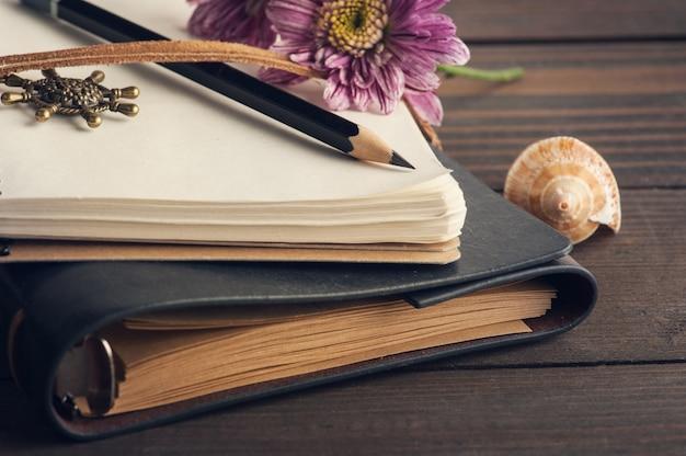 空白のノートブック、キャンドル、花を開く