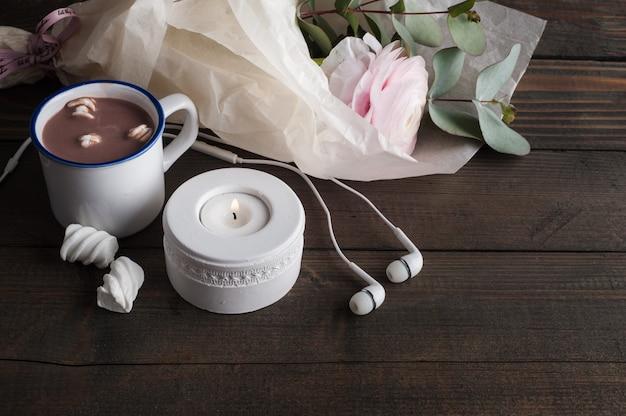 ピンクのラナンキュラス、ヘッドフォン、ホットチョコレート