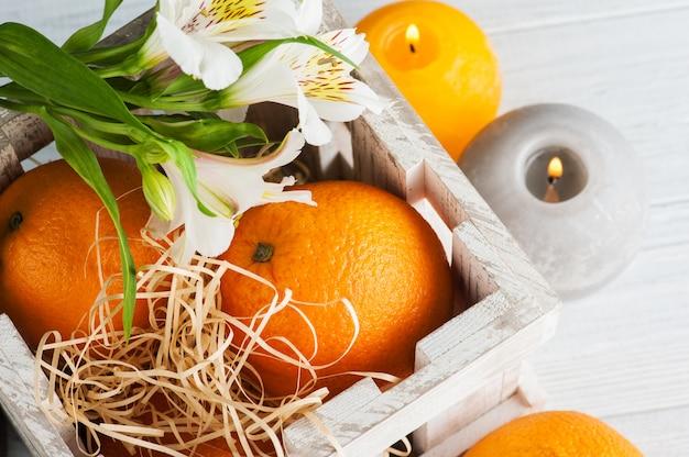 Апельсины в деревянной коробке, зажженные свечи