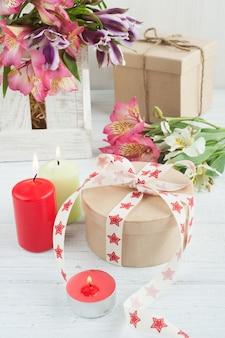 Цветы альстромерии в деревянной коробке, зажженная свеча