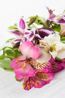 木製の背景にアルストロメリアの花