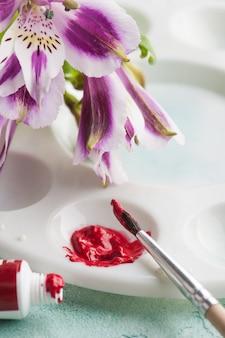 ペイントブラシ、春の花と赤い水彩絵の具