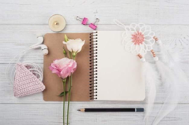 空白のノートブック、ピンクのかぎ針編みホルダー、イヤホン