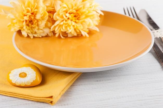 木製テーブルの上の皿に菊の花