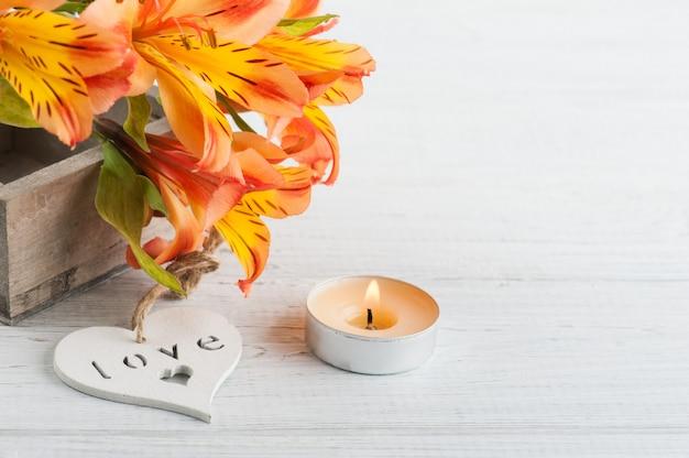 木製の箱、ハートのオレンジ色のユリの花のアレンジメント