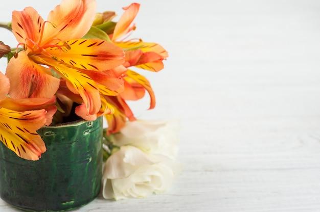 緑の鍋にオレンジ色のユリの花のアレンジメント