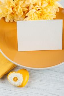 木製のテーブルの上の皿にクリサンテマムの花