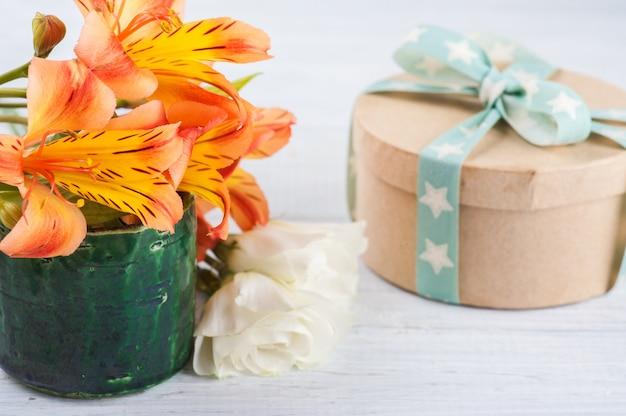 グリーンポット、ギフトボックスにオレンジ色のユリの花のアレンジメント