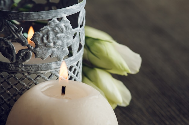Зажженные свечи и белые цветы на темном деревенском столе