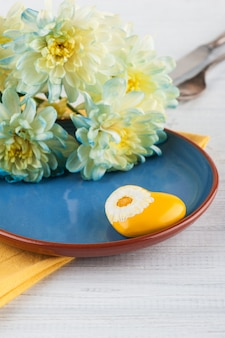 木製のテーブルのプレートに菊の花