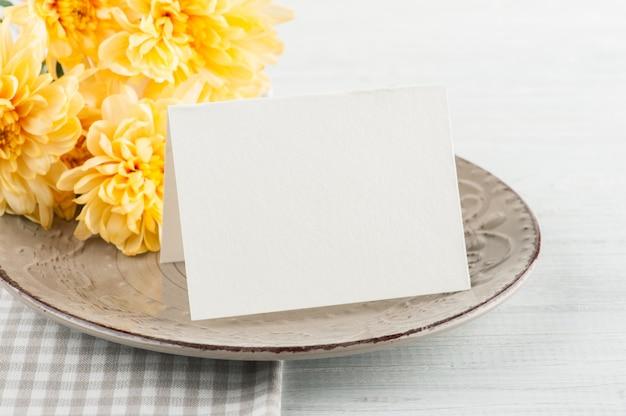 木製のテーブルの上の皿の上の菊の花