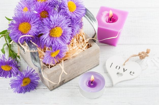 紫のヒナギクと白いテーブルの上のろうそくを点灯