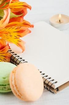 Пустой блокнот, зеленые оранжевые миндальные печенья, цветы